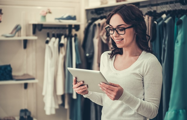 Woman with iPad in clothes store symbolising lean times for retailers